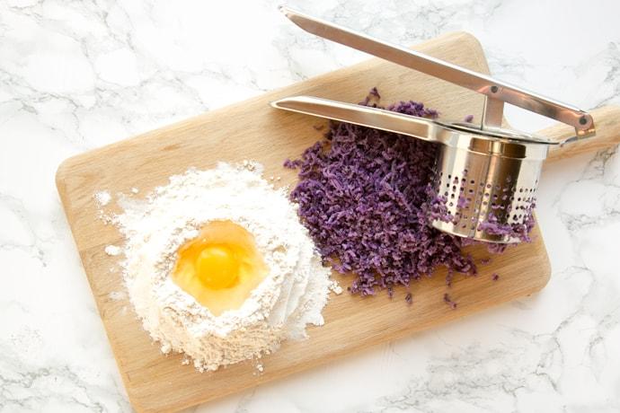 egg cracked in a small mountain of flour, next to potato ricer and purple potato mixture.