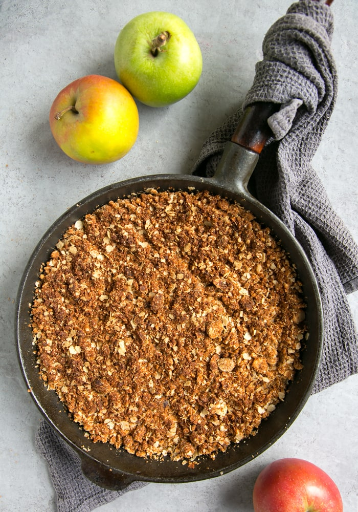 vegan apple crumble in cast iron skillet. with grey kitchen cloth beneath and green and red apples on the side.