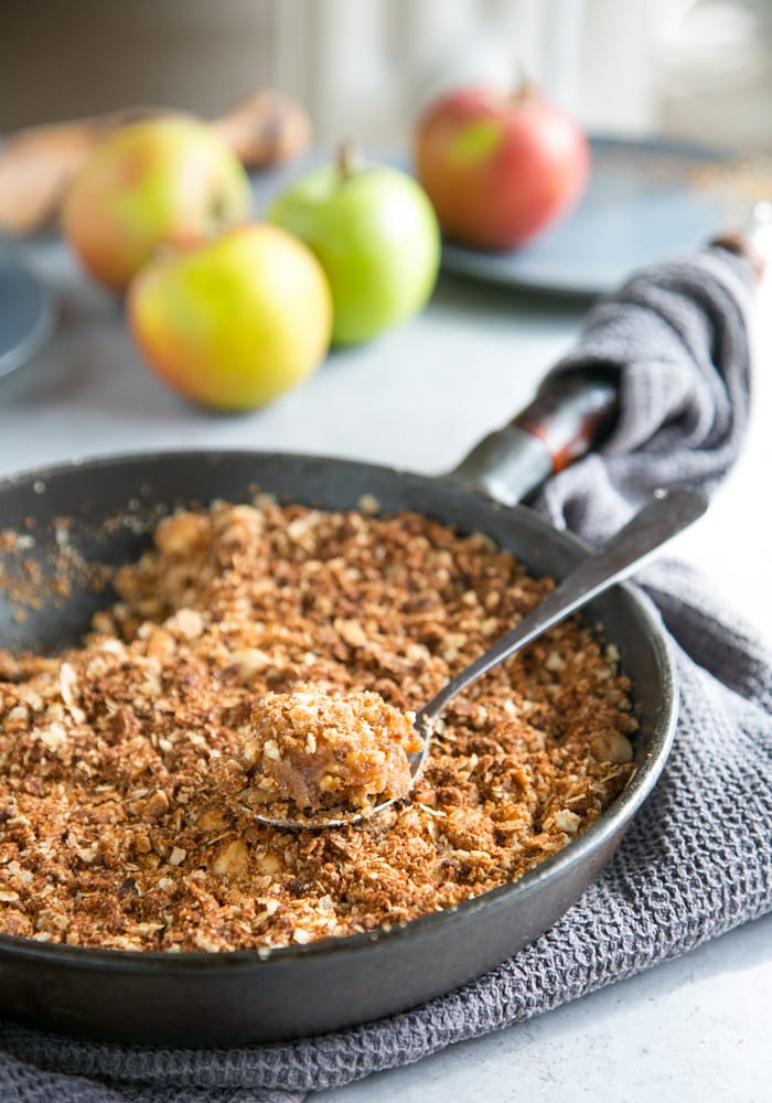 spoon with vegan apple crumble in focus, in a cast iron skillet, with grey kitchen cloth beneath and green and red apples on the side.
