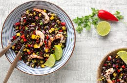 venere black rice salad with shrimps and mango salsa in a bowl, with lime and chili pepper on side