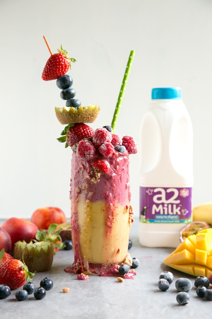 fruit freakshake in a glass topped with fresh fruit and bottle of a2 milk in the background