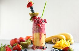 fruit freakshake in a glass topped with fresh fruit and mixed fruits all around