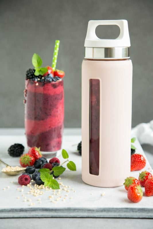 sigg bottle filled with mixed berry smoothie, and smoothie in tall glass decorated with berries, mint and green stroll, on white marble board, berries and a spoon with puffed quinoa
