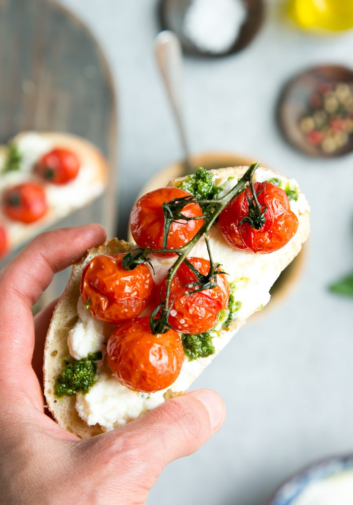 hand holding cherry tomato confit bruschetta with ricotta and basil pesto