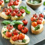confit tomato bruschetta with ricotta and basil pesto over a wood board