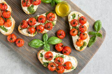 Cherry tomato confit bruschetta with ricotta and basil pesto over wood board
