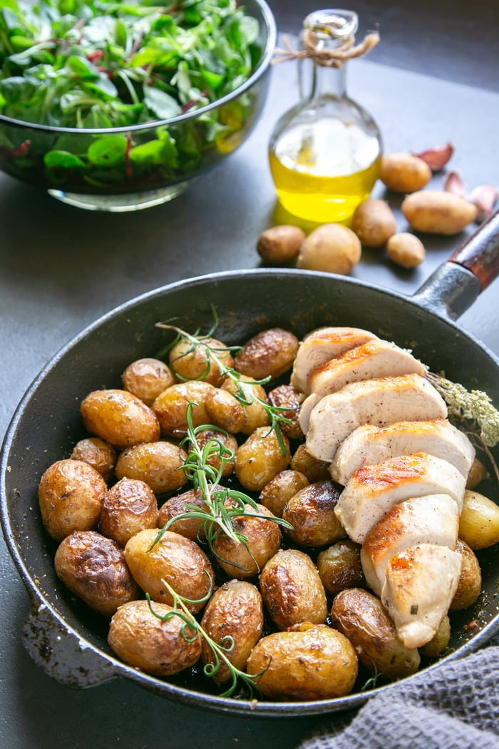 Italian pan roasted new potatoes with rosemary in skillet with grilled chicken breast, olive oil bottle, salad in bowl and raw potatoes in the background