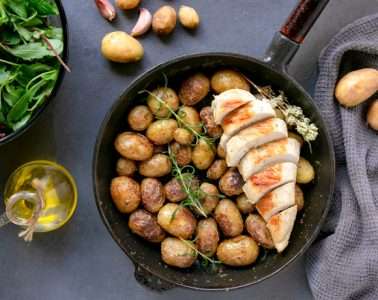 Italian pan=roasted new potatoes in skillet with grilled chicken breast, salad bowl and olive oil bottle on the left side, potatoes arranged on the background and grey towl on the right side