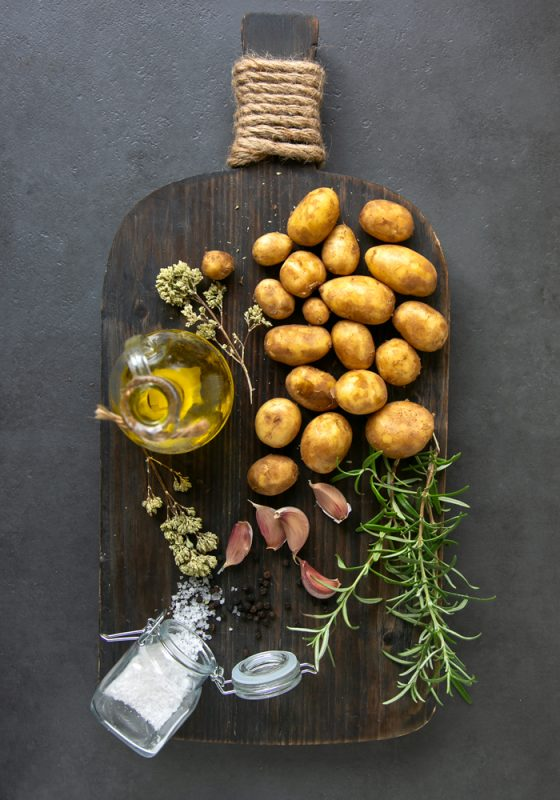 recipe ingredients: potatoes, olive oil bottle, rosemary sprigs, garlic, oregano sprigs and sea salt on a chopping board