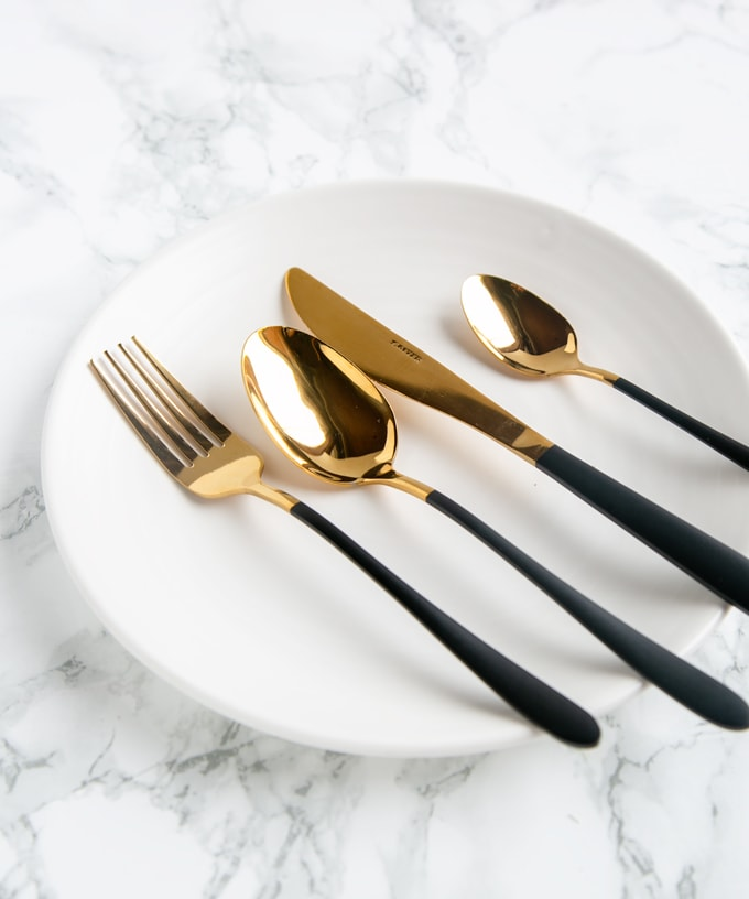 Foodie Gift Guide: Black and Gold cutlery set on a white plate and marble background
