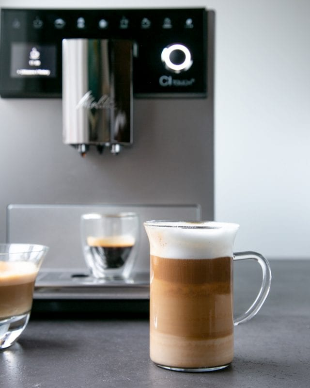 Foodie gift guide: Melitta CI Touch coffee machine , latte macchiato in clear glass cup, espresso in clear mug in the background