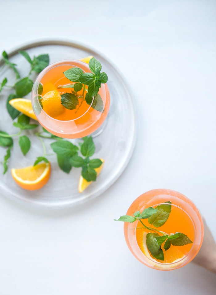 orange spritz in two glasses, one held by hand