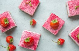 strawberry cheesecake bars and fresh strawberries on grey background