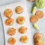 gluten-free blini topped with avocado cream and smoked salmon, served with lime wedges and avocado cream on the side