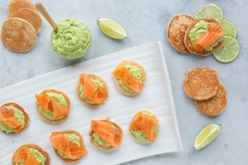 gluten-free blini topped with avocado cream and salmon, served with lime wedges and extra avocado cream on the side