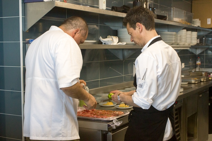 chef eduardo lalo garcia preparing food in the kitchen with kitchen staff