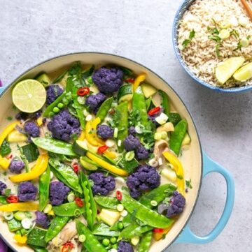 vegan thai green curry in large shallow pot with rice in a bowl and chopsticks on the side, and a purple napkin on the other side