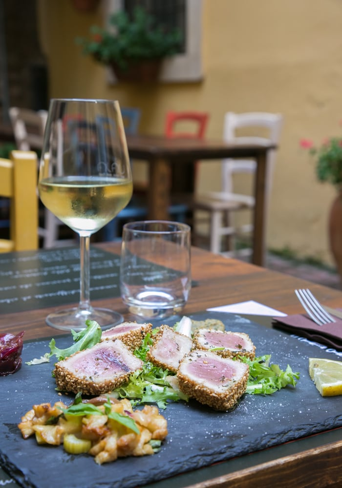 albacore tuna fillet in sesame crust, glass of white wine and restaurant background