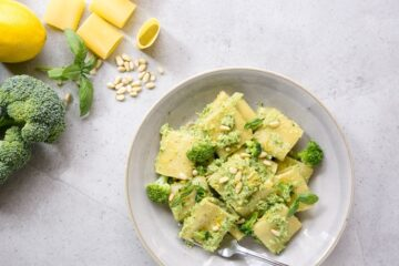 Broccoli pesto pasta on grey plate, raw broccoli, lemon, basil leaves, pine nuts and paccheri pasta in the background