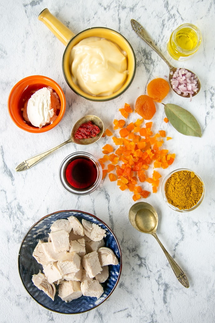 ingredients on a marble board: cooked chicken dried apricots mayonnaise crème fraîche olive oil curry powder white onion (or shallot) red wine bay leaf lemon juice a pinch of sugar salt & pepper