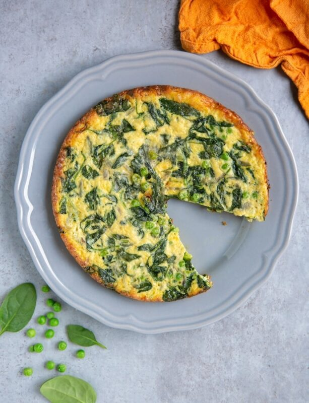 italian frittata with spinach and peas with one wedge removed on grey plate, next to orange cloth, and spinach leaves and peas for decoration