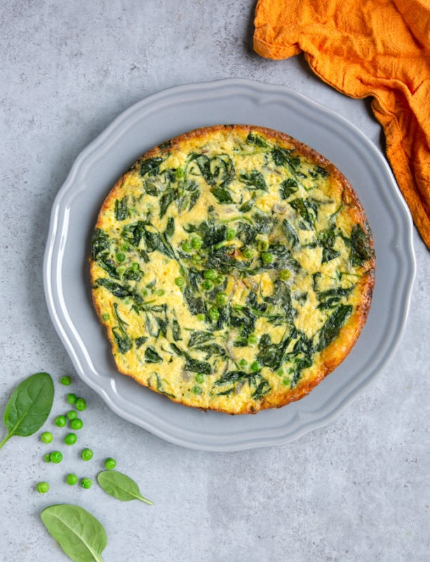 italian frittata with spinach and peas on large grey plate, next to orange cloth, and spinach leaves and peas for decoration