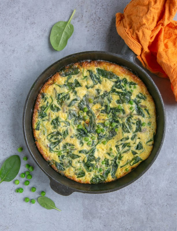 italian frittata with spinach and peas preparation step 5: cooked frittata in cast iron skillet, orange cloth covering the handle, spinach leaves and peas next to the skillet for decoration