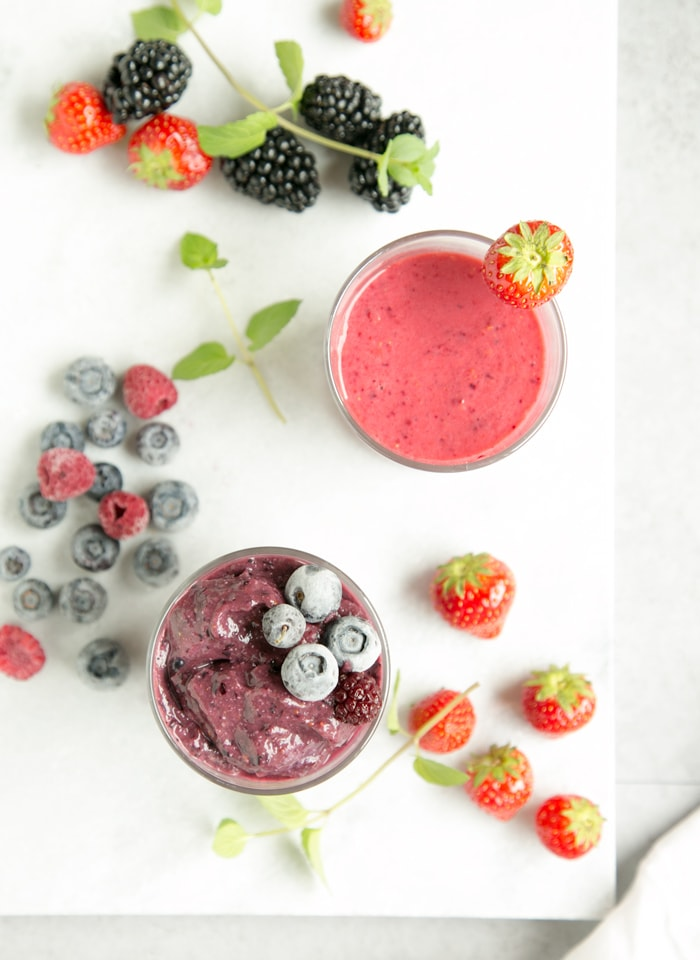 glass with blackberry and blueberry smoothie next to a strawberry and raspberry smoothie, mixed berries in the background over a white marble board