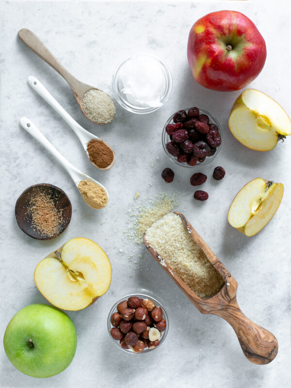vegan apple crumble ingredients: 1 red apple, half apple plus two extra slices, one green apple, 1 teaspoon of nutmeg, one teaspoon of ginger powder, one teaspoon of cinnamon, 1 tablespoon of sugar, one small pot with coconut oil, one small pot with cranberries, one small pot with toasted hazelnuts, and 1 flour spoon with almond flour.