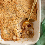 vegan apple crumble in a baking dish with golden spoon, a green napkin on the side
