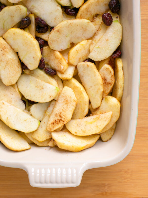 recipe step 1: sliced apples, cranberries, spices and sugar in a baking dish