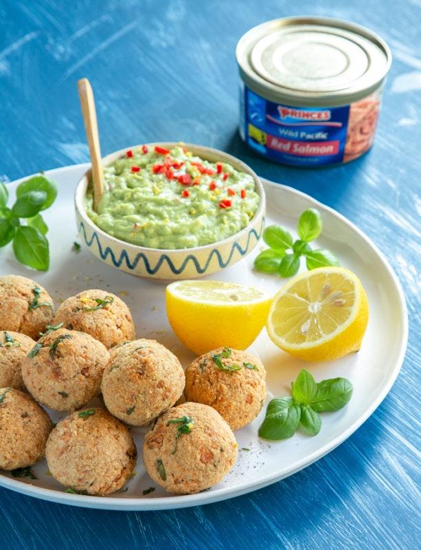 baked salmon meatballs on white plate served with halved lemon, basil leaves and avocado cream in a small pot, can of salmon in the background