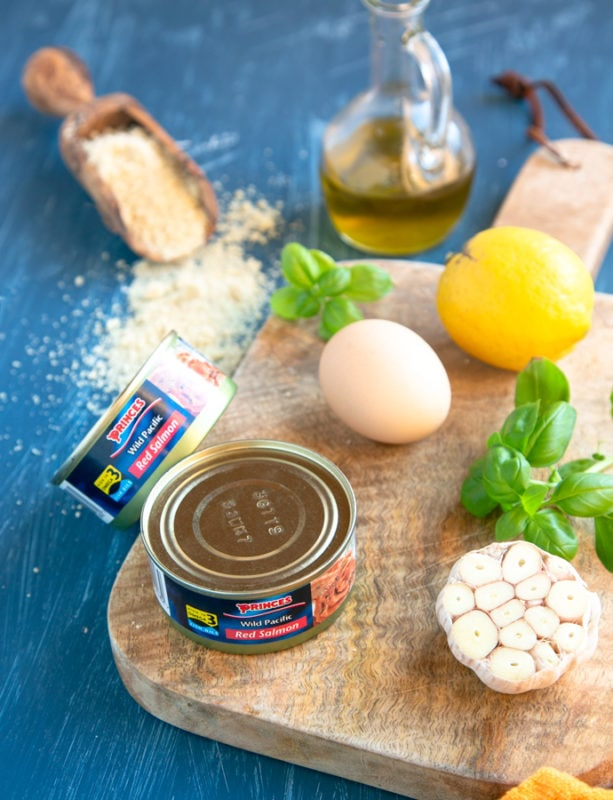 baked salmon meatballs ingredients: canned salmon, garlic, basil, lemon and egg on a wood board, almond flour and olive oil next to it