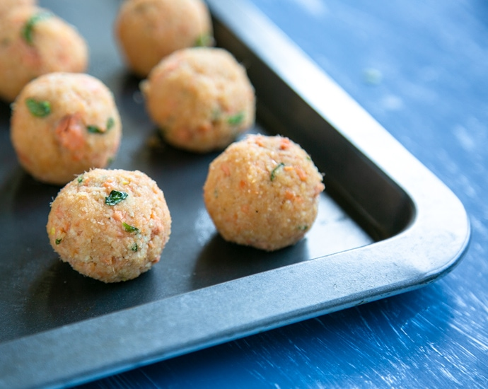 unbaked meatballs on a baking tray