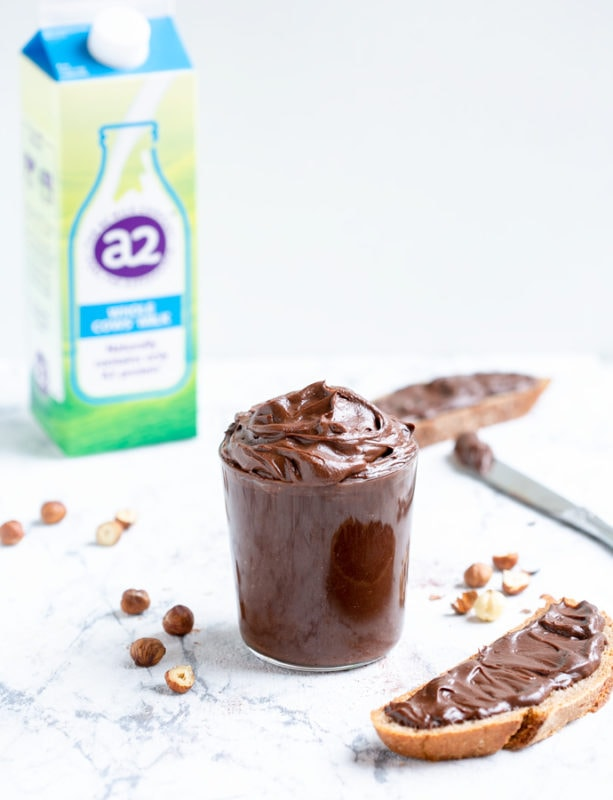 Italian chocolate hazelnut spread in large clear glass, bread slice with spread on the right side, knife with spread, a2 milk carton and hazelnuts on the left side