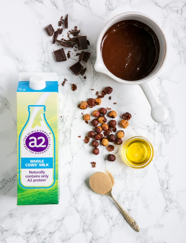 Italian chocolate hazelnut spread ingredients: a2 milk carton, hazelnuts, oil, spoon with brown sugar, chopped and melted chocolate in a white pot