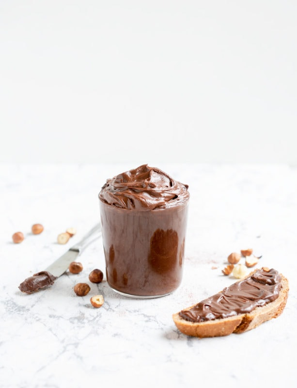 Italian chocolate hazelnut spread in large clear glass, bread slice with spread on the right side, knife with spread and hazelnuts on the left side