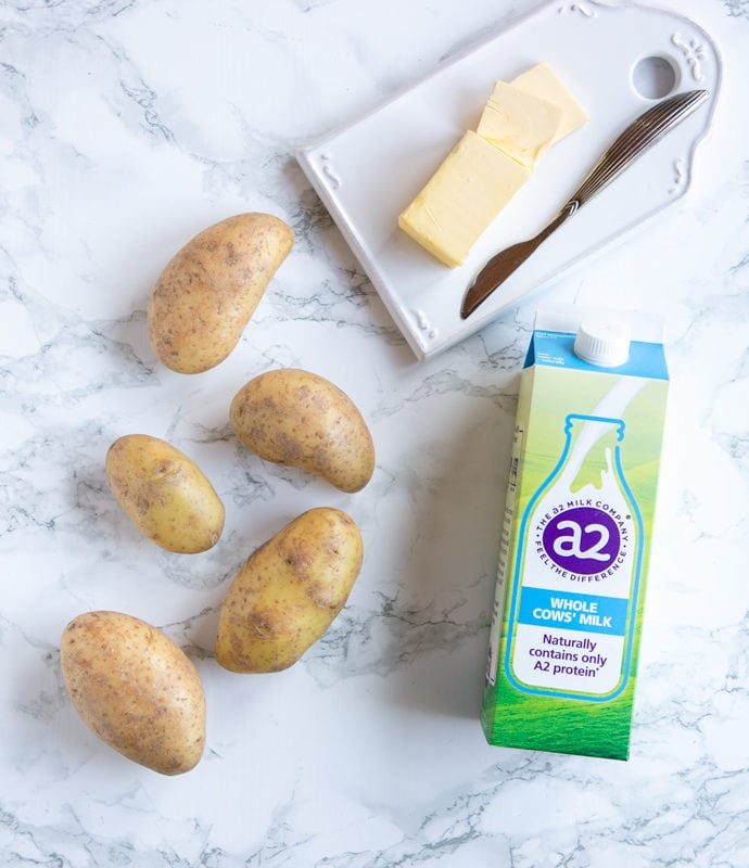 flat-lay image: five potatoes, butter and butter knife on white cutting board and carton of a2 Milk