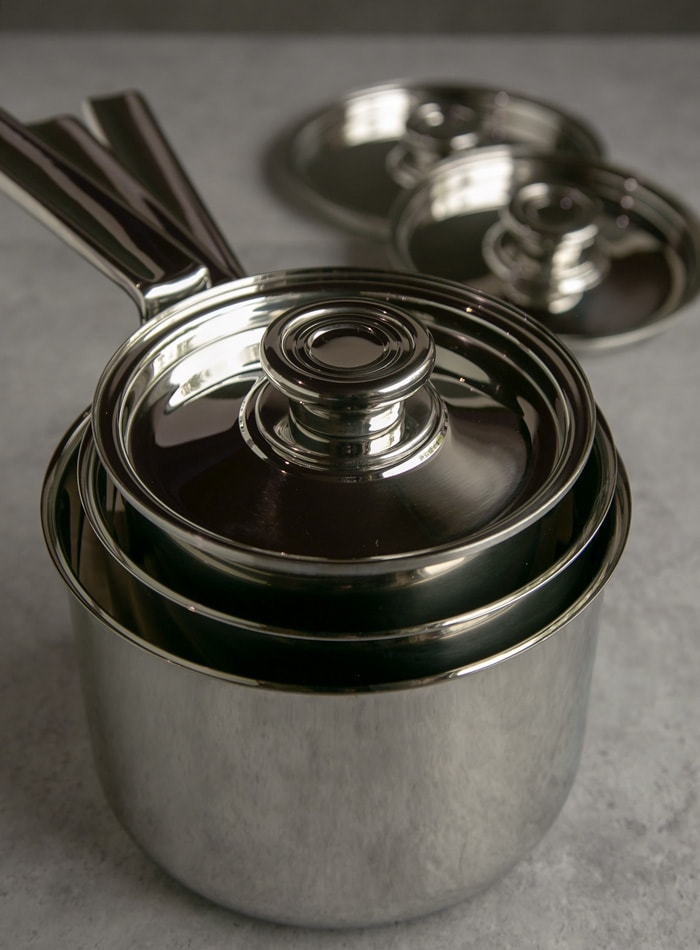 robert welch sauce pan set stacked together and lid on top and in the background