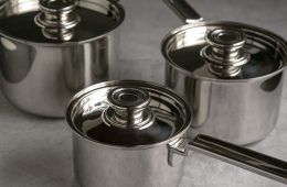 robert welch 3 saucepan set with lids, on grey background