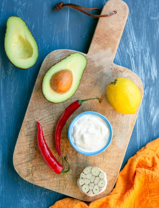 avocado dip ingredients: halved avocado, lemon, pot with yogurt, 2 red chili, halved garlic on a wood board, orange napkin next to the board