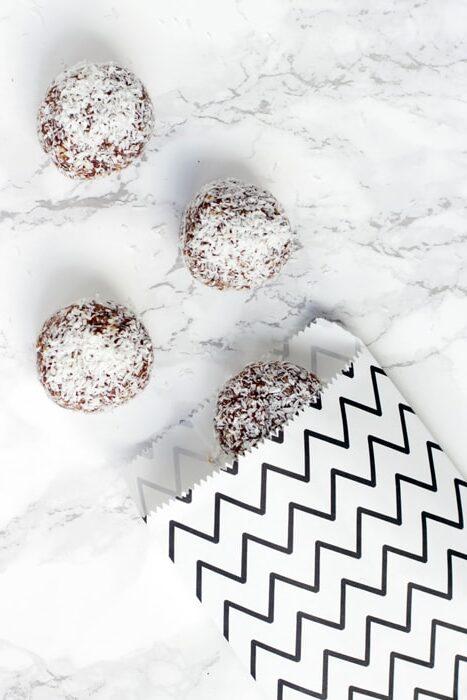 three swedish chocolate balls and a small white and black bag.