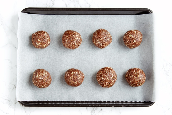 recipe step 3: mixture rolled into balls and placed on a baking tray covered with parchment paper.