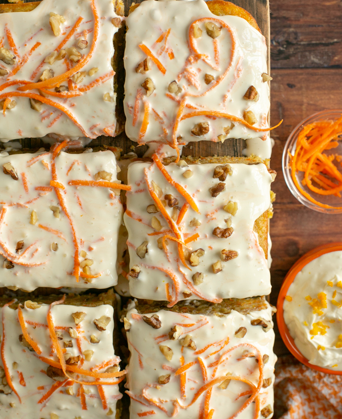 squares of carrot cake topped with mascarpone cream, sliced carrots and chopped nuts.