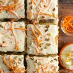 american carrot cake with mascarpone frosting cut into squares and topped with sliced carrots and chopped nuts.