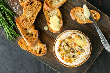 baked camembert in wooden box on a wooden board, next to a butter knife, toasted baguette slices, one bread slices with melted cheese on top, sprigs of rosemary and sea salt flakes.