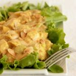 coronation chicken topped with toasted almond flakes on a bed of salad leaves