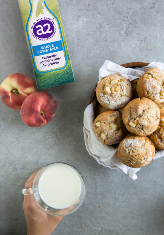 peach muffins in a bowl covered with a white napkin, a2 milk carton on the top left side next to 2 peaches, hand holding a cup of milk on the bottom left side.