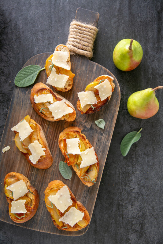 Bruschetta with Caramelised Pears and Grana Padano Riserva on a wood board, scattered sage leaves around and two pears on the top left side