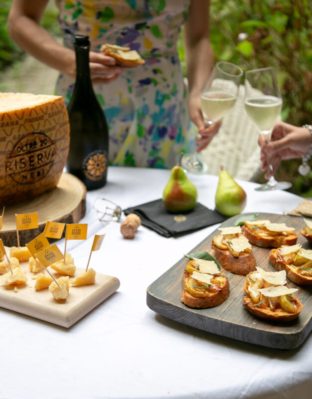 Table with a woodboard with Grana padano cheese pieces on the left, woodboard with bruschetta with caramelised pears on the right, 2 pears on the back, lady holding a bruschetta in one hand and a glass of prosecco into the other toasting with another glass of prosecco. Prosecco bottle and wheel of grana padano cheese next to the lady.